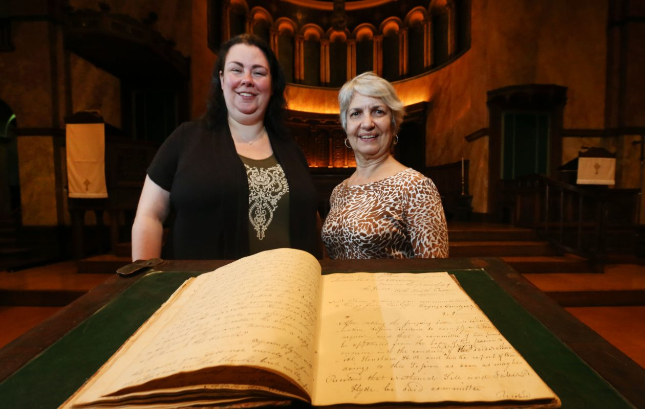 Church business manager Christina Banas, left, and interim Pastor Elena Delgado look over the book of handwritten notes documenting the church as the first of any denomination in Buffalo. (Sharon Cantillon/Buffalo News)