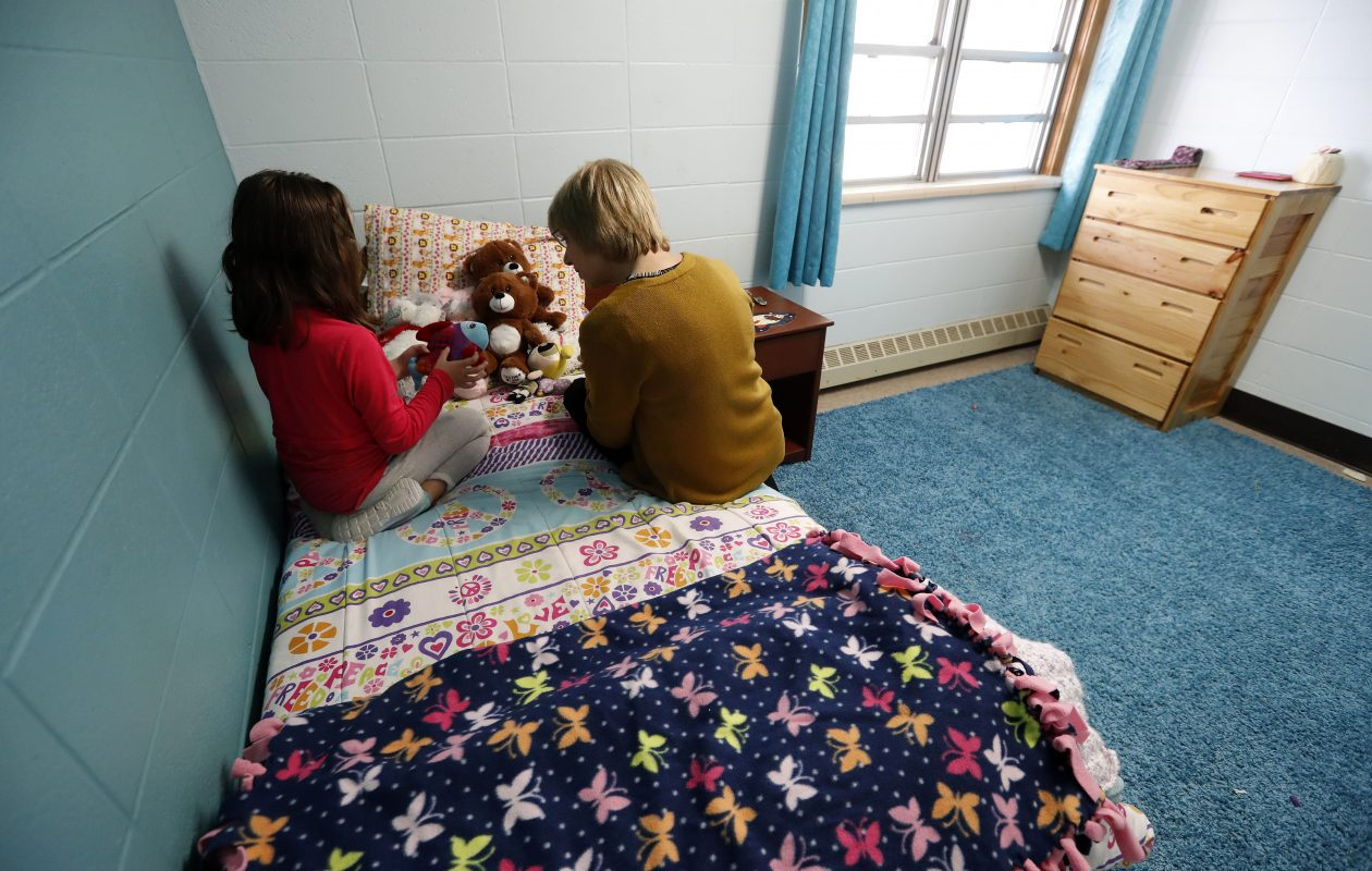 Halli Lavner, a director with Baker Victory Services, speaks with a child at the Nelson Cottage in Lackawanna, which serves as a temporary shelter for children in need of emergency foster care services. (Mark Mulville/Buffalo News)