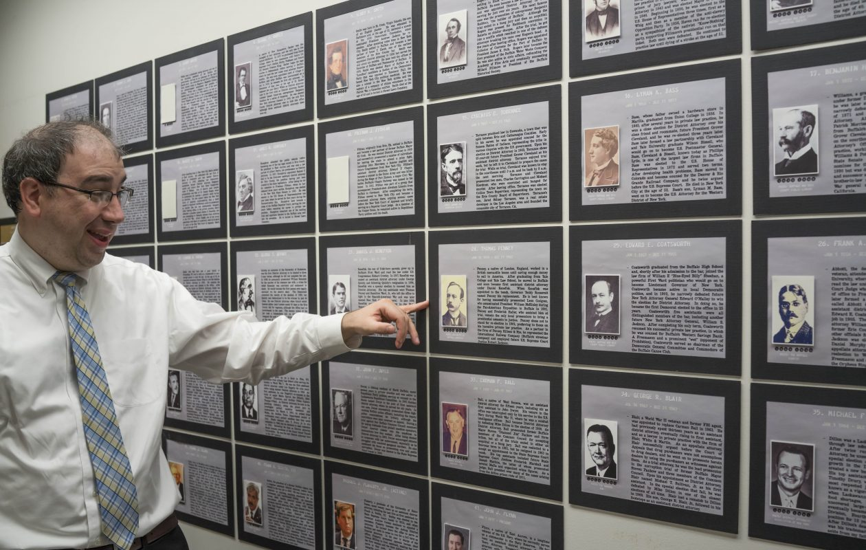 Assistant District Attorney David Heraty, the unofficial office historian, has compiled biographies of every DA in Erie County history in the new 'History Wall' display in the District Attorney's Office. He's pointing out Thomas Penney, who successfully prosecuted President McKinley's assassin in 1901. The Erie County District Attorney's Office is the only county office to have brought a presidential assassin to justice.  (Derek Gee/Buffalo News)