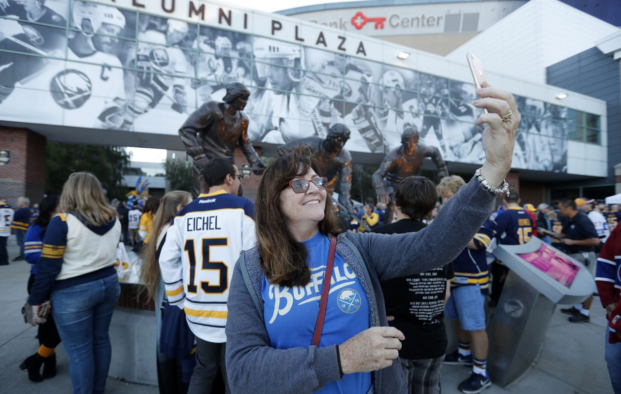 Susie Jackson of East Aurora takes a selfie with the French Connection statue before the Sabres' home opener on  Thursday, Oct. 5, 2017. (Mark Mulville/Buffalo News)