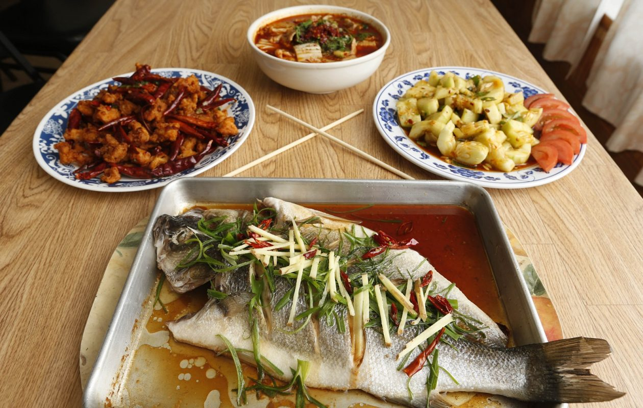 Clockwise from foreground is the steamed bronzino sea bass, hot chile chicken, poached spicy slices of pork and Slip Cucumber, all from Peking Quick One. (Sharon Cantillon/Buffalo News)
