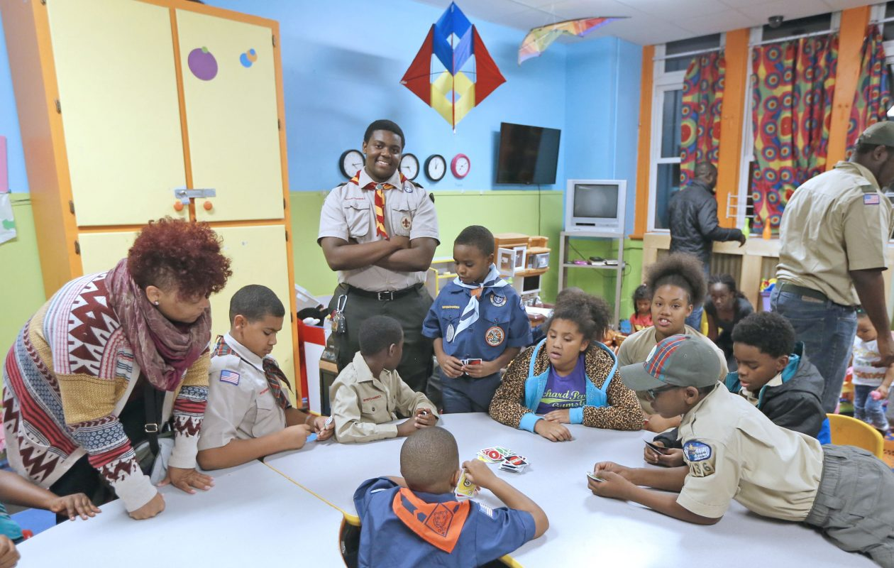 Aspiring Eagle Scout Jeffrey McMillan, standing, oversees game night at the Vive shelter, which he organized to help refugee kids learn English and feel more at home in Buffalo. (Robert Kirkham/Buffalo News)
