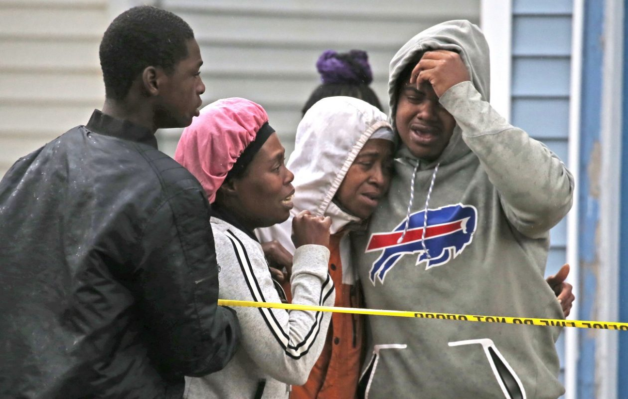 Friends and family members console each other after learning the identification of the 25-year-old man shot and killed on Kensington Avenue on Monday. (Robert Kirkham/Buffalo News)