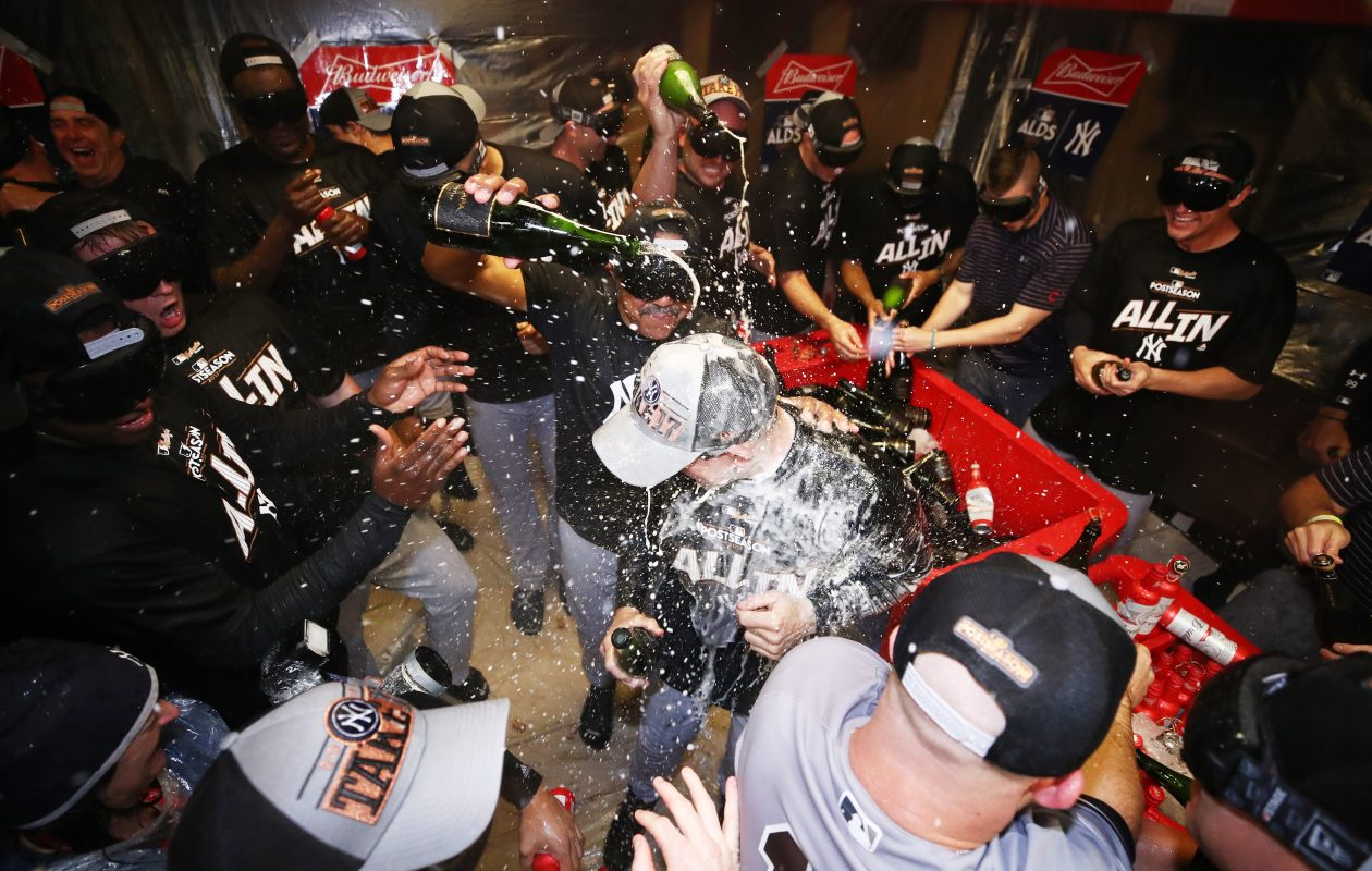 The New York Yankees celebrate in the locker room after their 5 to 2 win over the Cleveland Indians in Game Five of the American League Divisional Series at Progressive Field on Wednesday in Cleveland. New Era staff helps distribute the goggles and series-clinching caps. (Gregory Shamus/Getty Images)