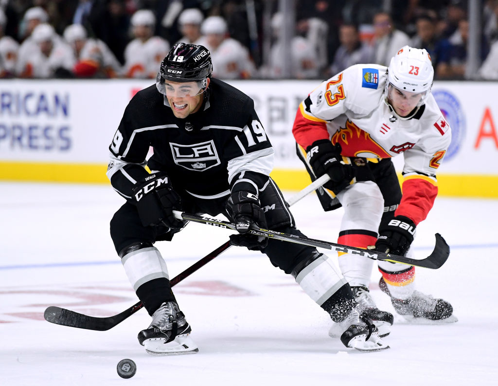 Eden native Alex Iafallo of the Los Angeles Kings skates away with the puck from the check of Calgary's Sean Monahan during the Kings' overtime loss to the Flames Wednesday in Staples Center. (Getty Images)