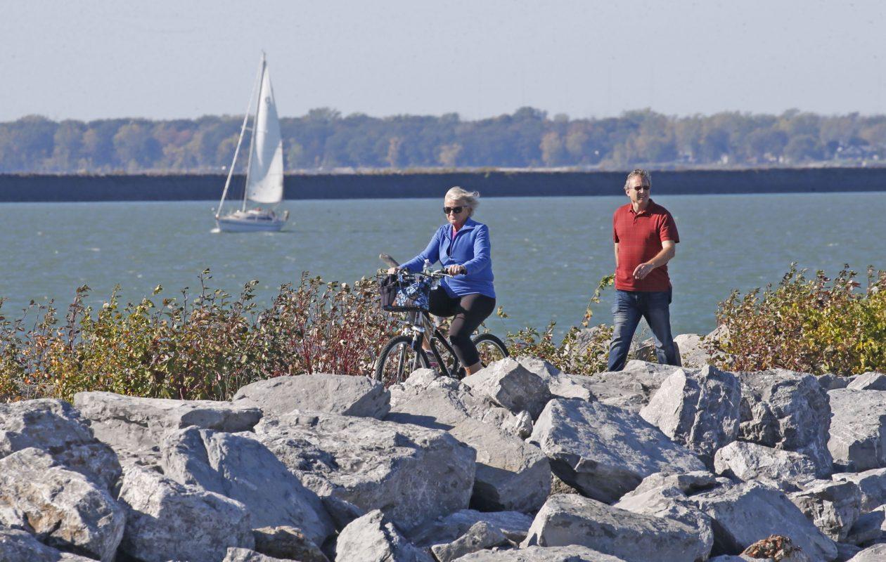 A bicyclist and a hiker walk along the breakwater at Buffalo Harbor State Park, off Fuhrmann Boulevard, on Wednesday, Oct. 18, 2017.  (Robert Kirkham/Buffalo News)