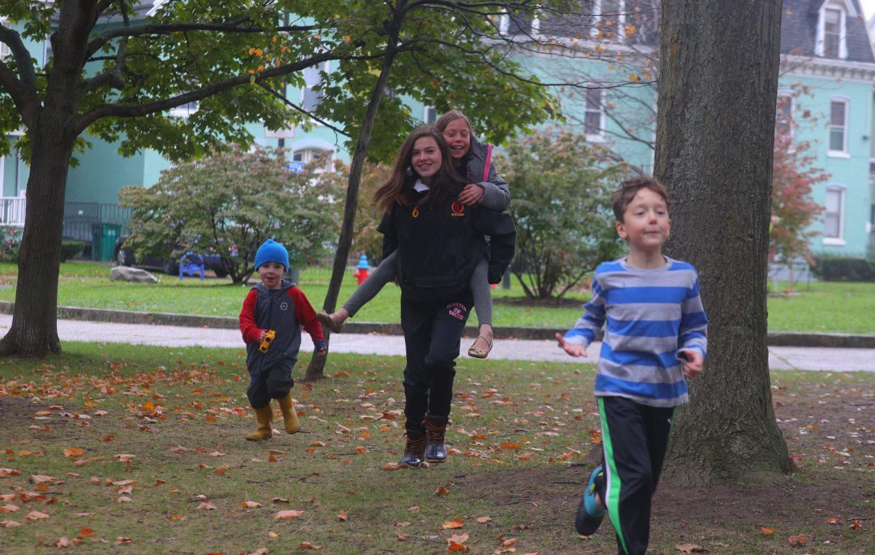 Playing in Buffalo's Days Park are, from left, Miles Weber, 4, Brianna Grine, 16, giving a piggyback ride to Addie Hann, 9, and Orlando Hann, 7, on Saturday, Oct. 28, 2017. Days Park is an oval-shaped, 1.5-acre park full of oak trees and Victorian lamp posts. The Days Park Block Club helped revive the park and recently received an award for its  efforts. (John Hickey/Buffalo News)