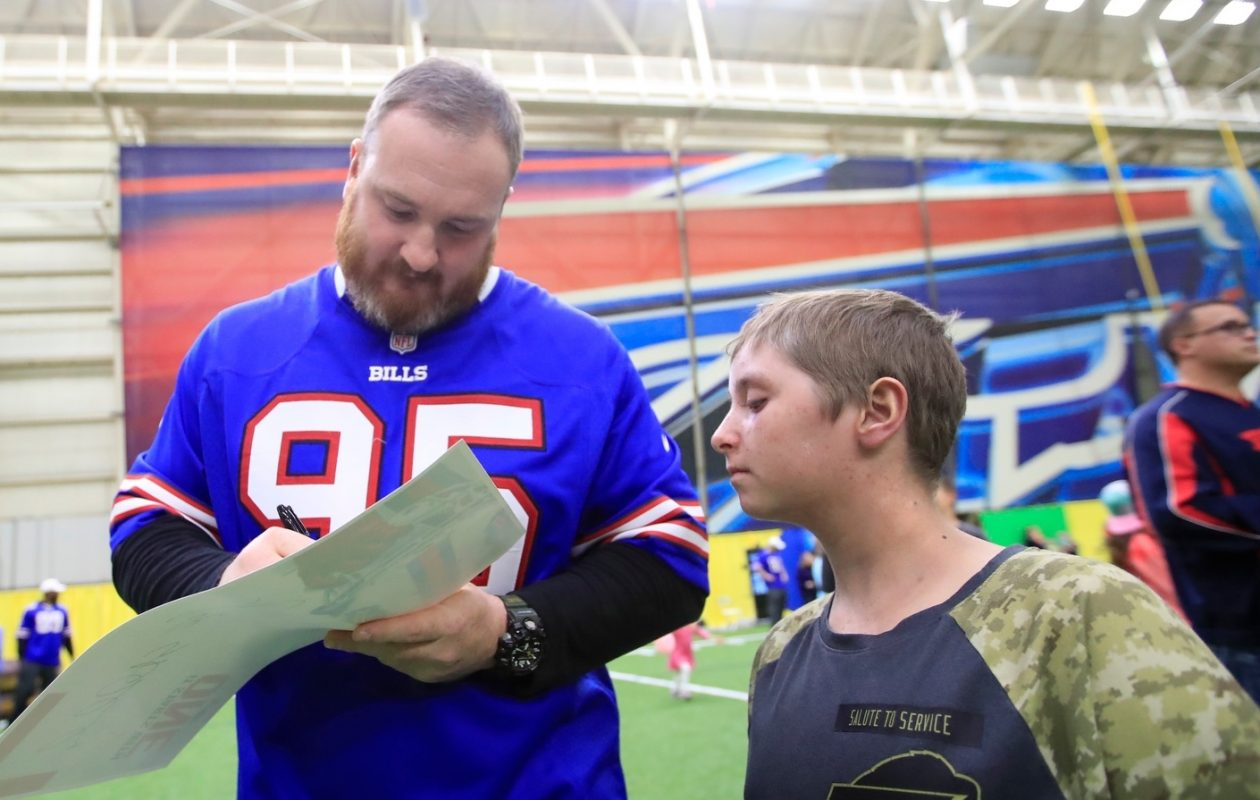 Bills player Kyle Williams signs an autograph for Jack Frost III during Tuesday's family fun night for children with pediatric cancer at the ADPRO Sports Training Center in Orchard Park. (Harry Scull Jr./Buffalo News)