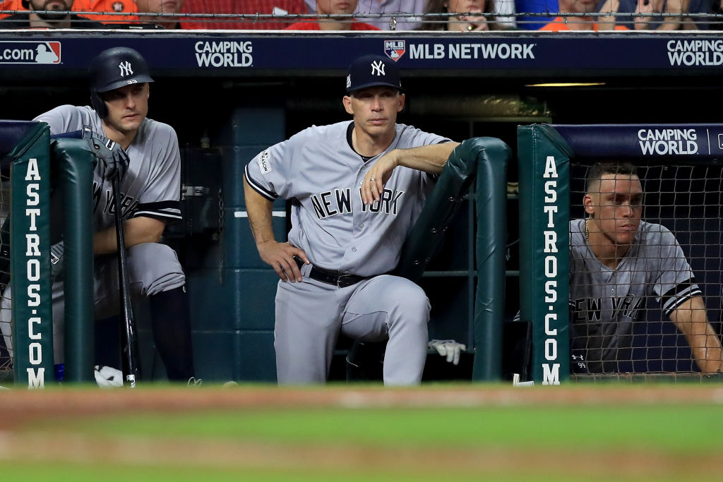 Joe Girardi is flanked by Greg Bird, left, and Aaron Judge as the final outs are made during Game Seven of the ALCS Saturday night in Houston (Getty Images).