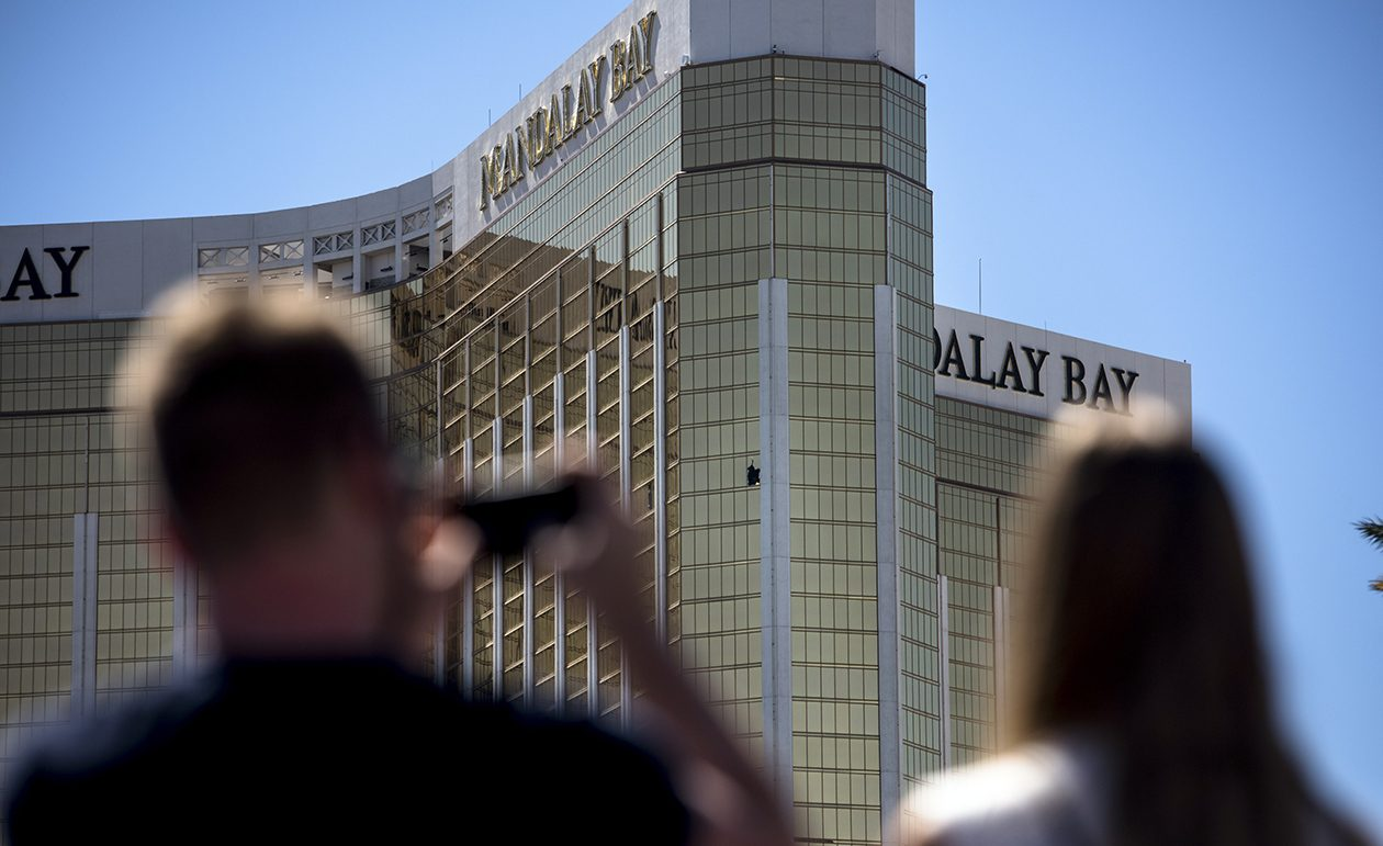 Pedestrians take photos of the broken windows on the 32nd floor of Mandalay Bay, where a gunman fired on an outdoor concert festival Sunday. Two Amherst residents were staying in the hotel at the time. (New York Times)