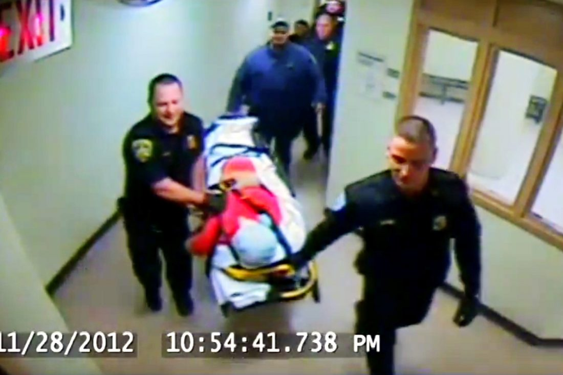 Inmate Richard A. Metcalf Jr., with his head face down and covered by a pillow case, is rolled out of the Erie County Holding Center by two jail sergeants on Nov. 28, 2012. This image is from a jail video camera.