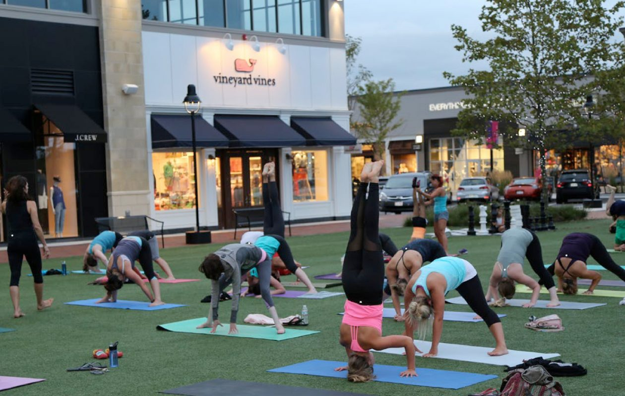 A scene of people doing yoga on the green at WS Development's MarketStreet shopping center in Lynnfield, Mass. WS plans a similar gathering space at its redeveloped Northtown Plaza in Amherst. (Photo courtesy of WS Development)
