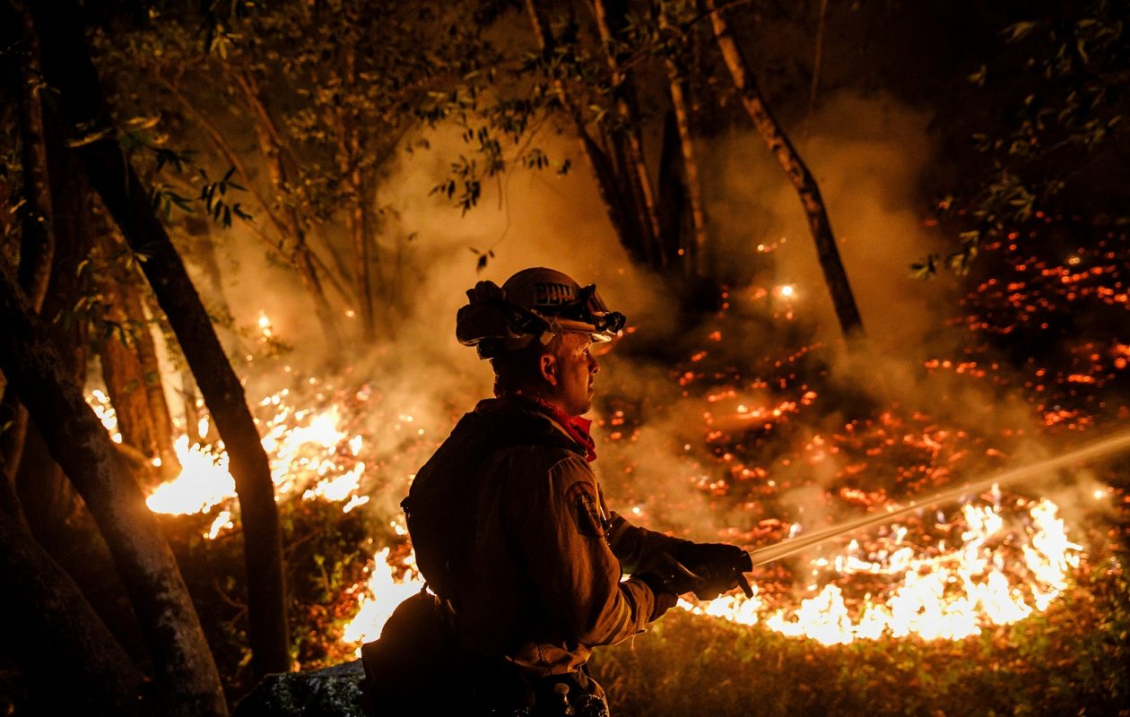 Firefighter Mario Topete attacks flames as his unit tries to prevent a fire from crossing Highway 29 north of Calistoga on Oct. 12. (Marcus Yam/Los Angeles Times/TNS)
