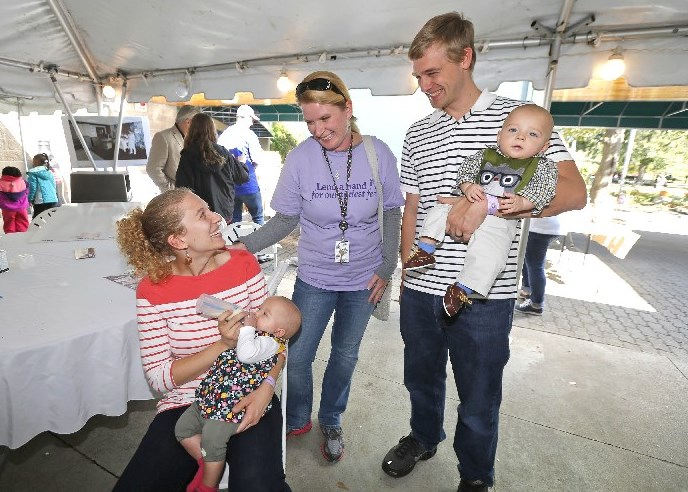 Physical therapist Wendy Gonzalez, center, visits with mother Heather Coles, holding Hannah, and dad John, holding brother Andrew, both 8 months. The twins were born 13 weeks early and are doing fine. There was a reunion picnic at the Buffalo Zoo with families who had babies in Sisters Hospital neonatal intensive care unit with doctors, support staff and nurses who saved them Sunday. (Robert Kirkham/Buffalo News)