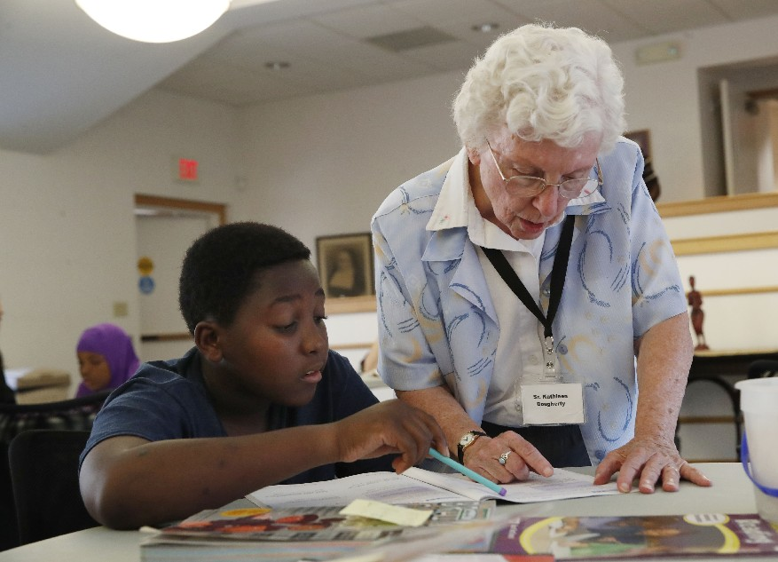 Sister Kathleen Dougherty, right, helps Lugundi Hassan 12, with his 7th grade reading and math during a gathering of the Somali Bantu afterschool program at St. Mary Center on the West Side. Dougherty is a coordinator and is one of the founders. (Sharon Cantillon/The Buffalo News)