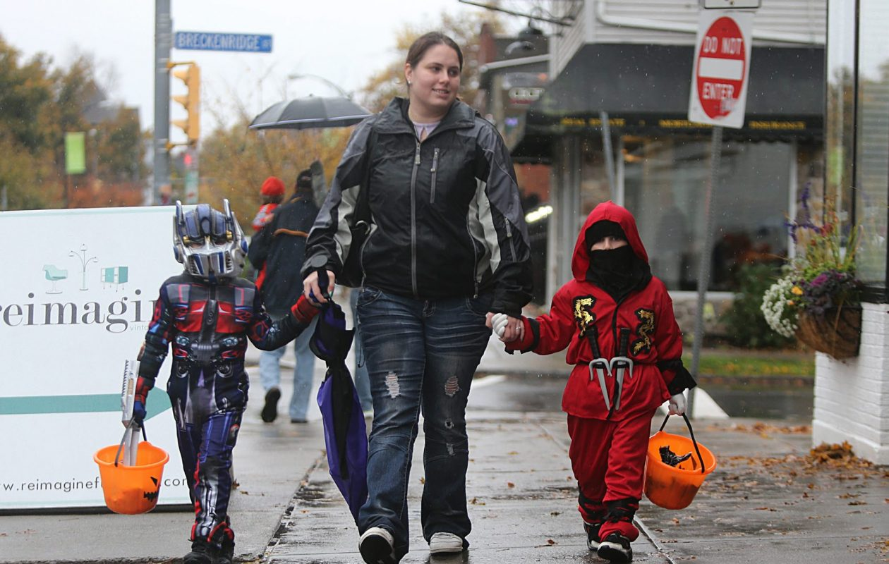 Toni Rogers, of Buffalo, strolls along Elmwood Ave. with her sons, Daylen Long, 4, left, and Donte Long, 5, as they go trick or treating at businesses participating in a Halloween candy handout in 2012. (News File Photo)