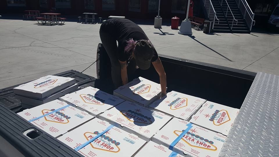 An unidentified volunteer helps prepare Naked City pizzas for delivery Monday to medical staff and emergency responders. (Photo courtesy Chris Palmeri)