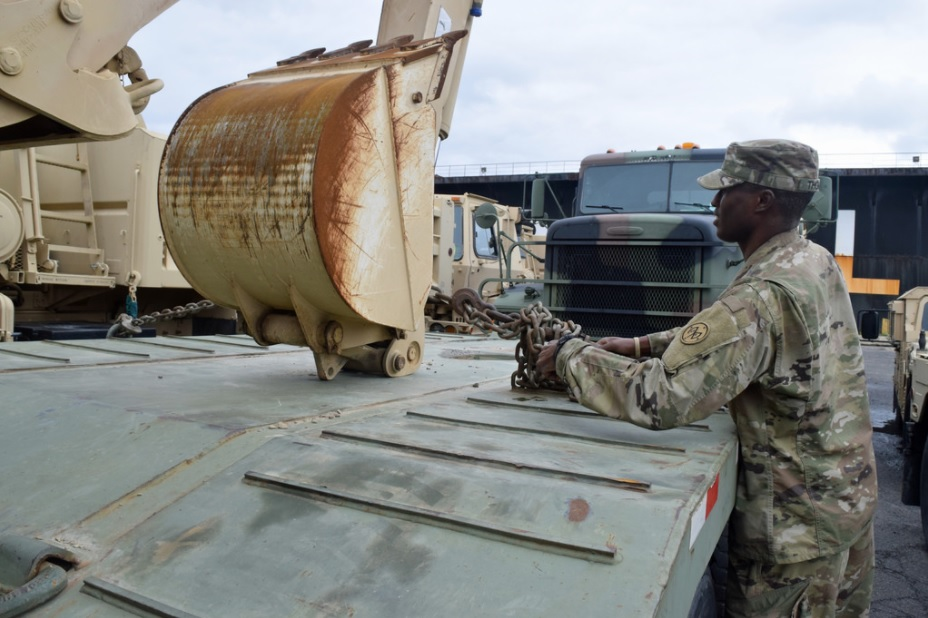 Sgt. DaVon Thomas, of the 27th Brigade Special Troops Battalion, checks tie downs on one of more than three dozen vehicles from the Buffalo-based 152nd Engineer Support Company that are being shipped by barge to Puerto Rico. (Photo courtesy of New York National Guard)