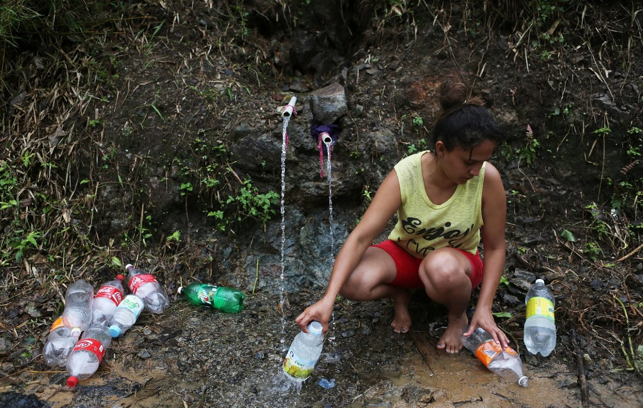 In this Oct. 10 photo, Yanira Rios collects spring water for use in her house, which is without running water or electricity, nearly three weeks after Hurricane Maria hit the island. (Getty Images)