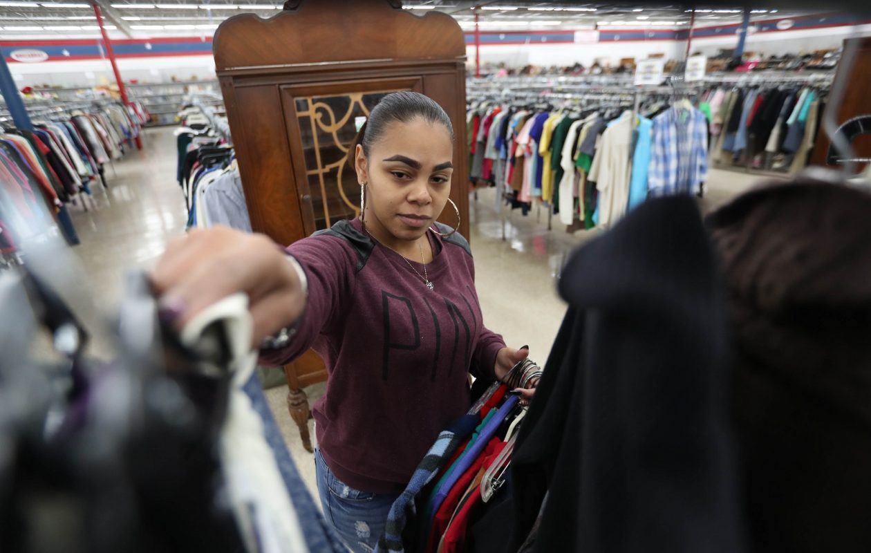 Amvets Thrift Store employee Shermara Jimenez brings out a rack of merchandise. (Sharon Cantillon/Buffalo News)