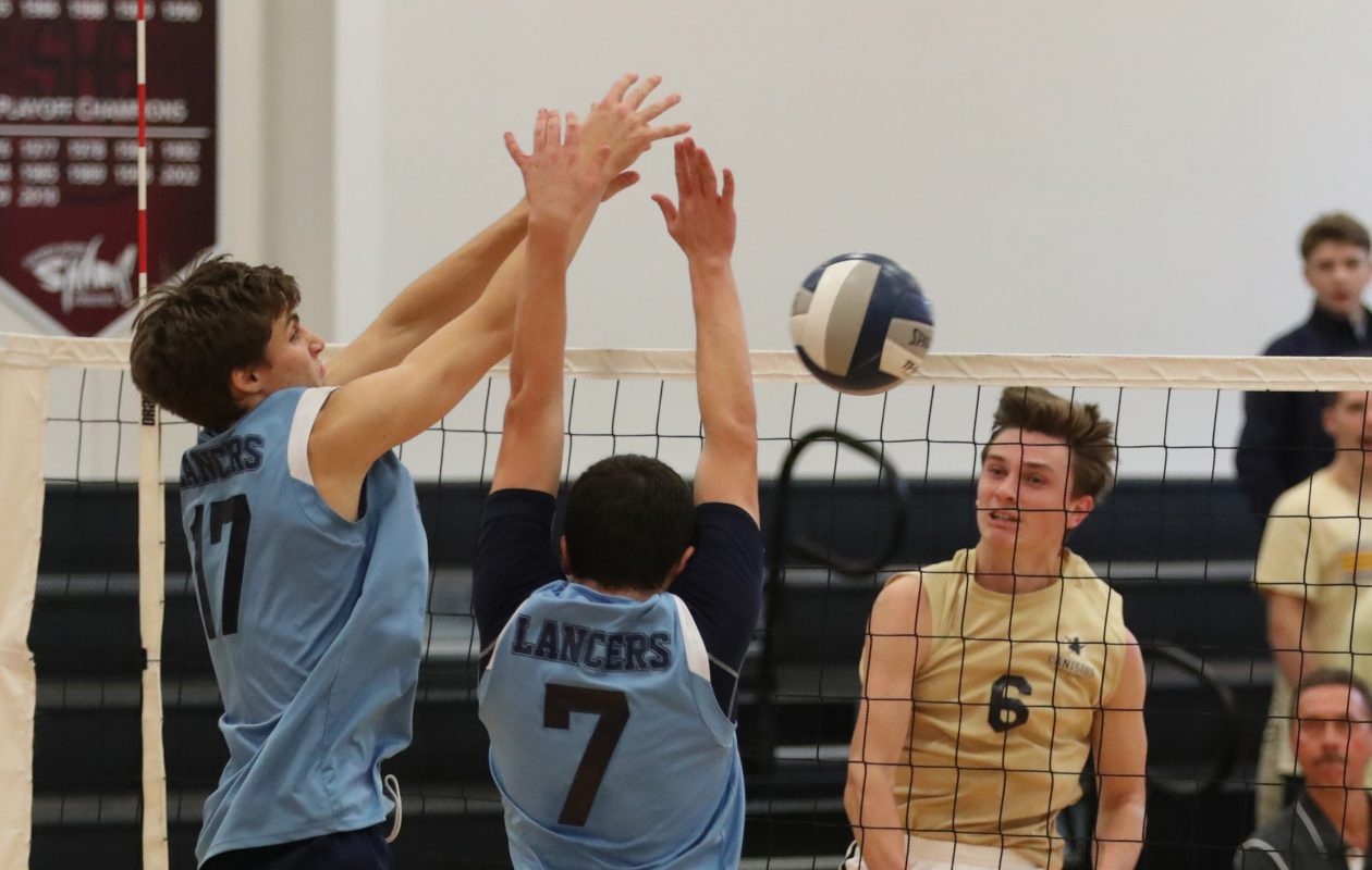 Troy Gooch of Canisius kills the ball and Christian Szablewski, left, and Austin Walsh of St. Mary's block the shot. (Sharon Cantillon/Buffalo News)