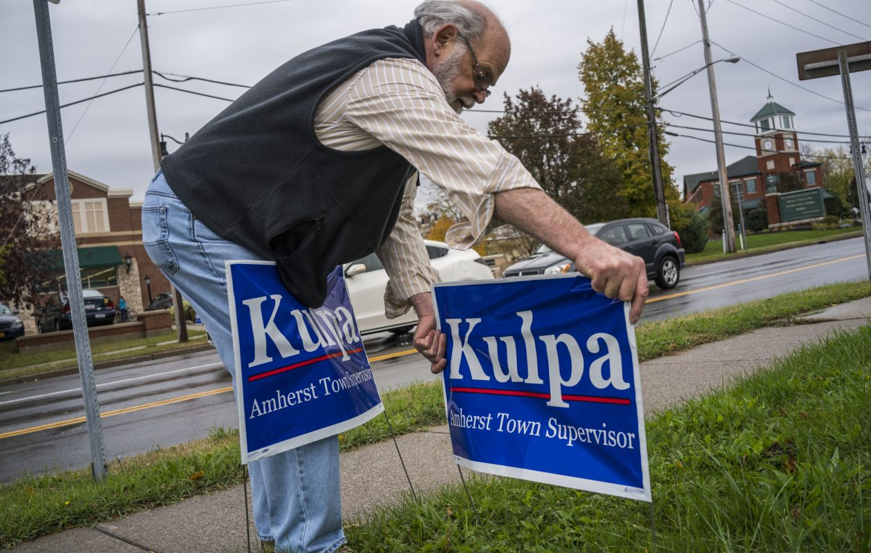 Tony Marconi, a volunteer for the campaign of Brian Kulpa for Amherst town supervisor, places signs on Union Road and Main Street on Sunday. (Derek Gee / Buffalo News)