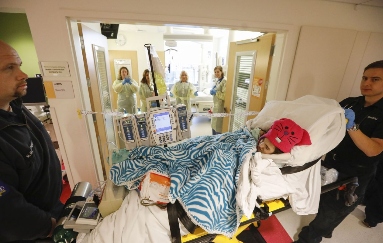 With EMT Michael McCafferty, left, and paramedic Nikolas Mofarden, right, of AMR, doing the driving, 12-year-old Olivia Reger arrives to applause from eager staff at the Pediatric Intensive Care Unit at the new John R. Oishei Children's Hospital, on Friday.  (Derek Gee/Buffalo News)