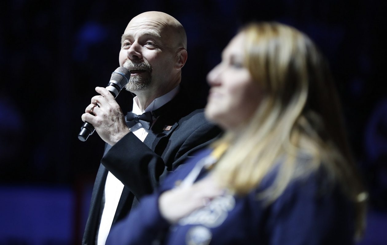 Doug Allen belts the Canadian and United States national anthems before the Sabres play the Washington Capitals on Nov. 7. At right is Navy veteran Brittney Bake. (Mark Mulville/Buffalo News)