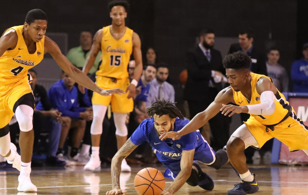UB guard Jeremy Harris , Canisius  guard Malik Johnson and Griffs forward Jalanni White battle for a loose ball.  (James P. McCoy/Buffalo News)