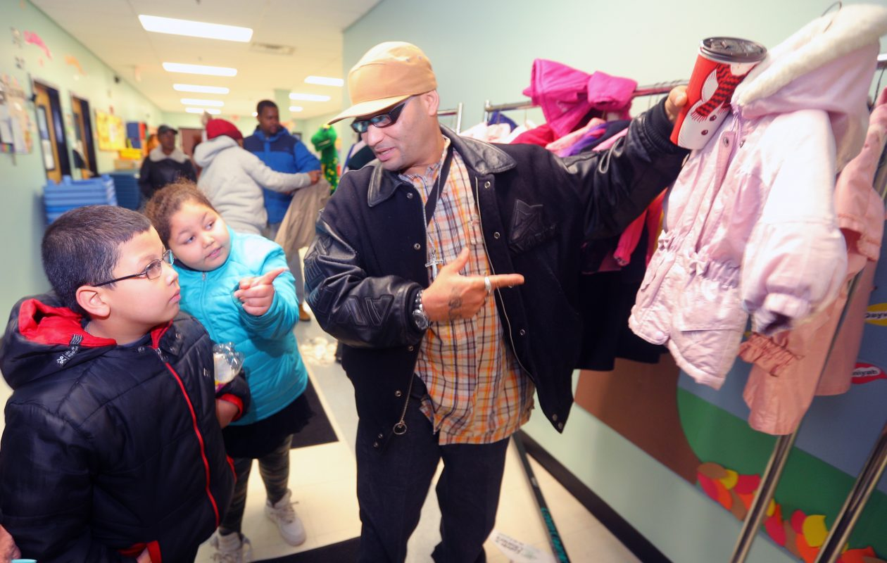 Justiliano Colon, right, asks his children, Alicia, 9, and Justin, 7, if a coat is right at the 22nd annual Colvin Cleaners Coats 4 Kids Program at True Bethel Baptist Church on Saturday, Nov. 11, 2017.   (John Hickey/Buffalo News)