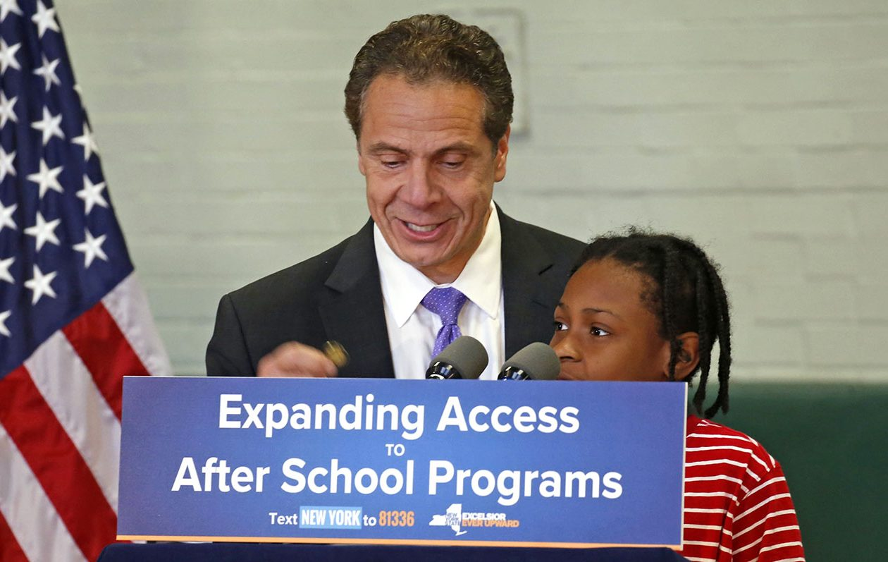 """Gov. Andrew M. Cuomo hands his New York State lapel pin as a prize to Tyree Scott, a third-grader, who guessed the magic word, """"love,"""" that officials say motivated the state's new """"Expanding Access to After School Programs."""" Cuomo spoke at an assembly at Hamlin Park School in Buffalo on Nov. 16. (Robert Kirkham/Buffalo News)"""