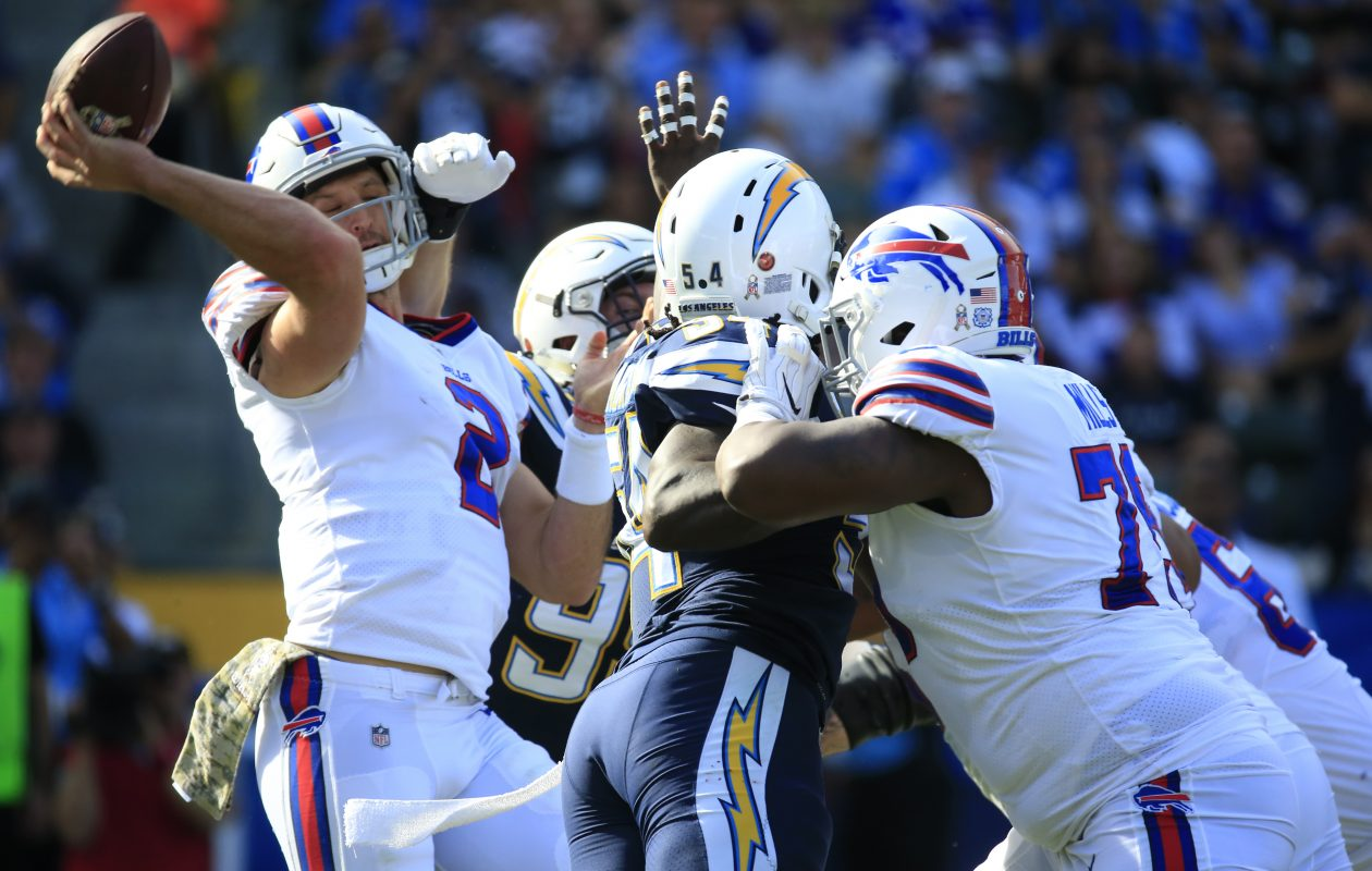 Buffalo Bills rookie Nathan Peterman gets hit while throwing in the first quarter; he would be intercepted by the Los Angeles Chargers' Casey Hayward. (Harry Scull Jr./ Buffalo News)
