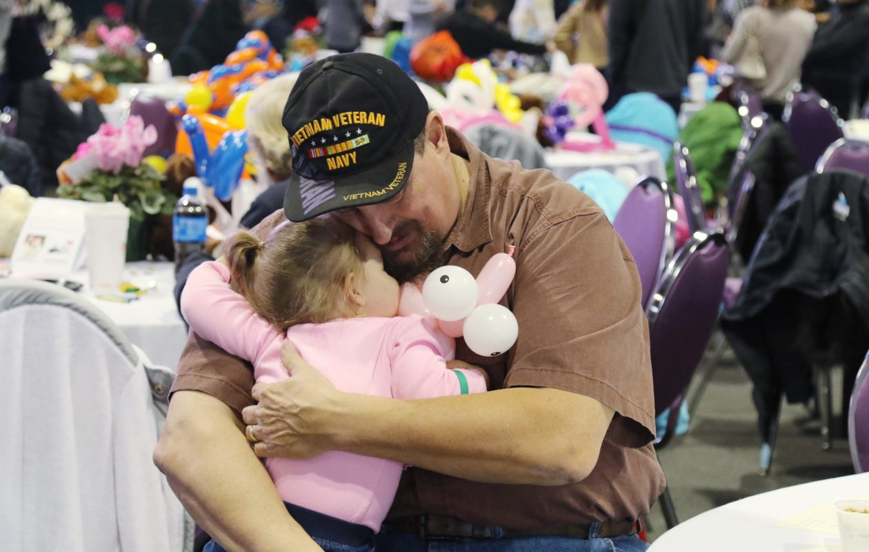 A father embraces his newly adopted daughter at a National Adoption Day ceremony in the Nicholas J. Pirro Convention Center, Syracuse. (Photo courtesy Herm Card)