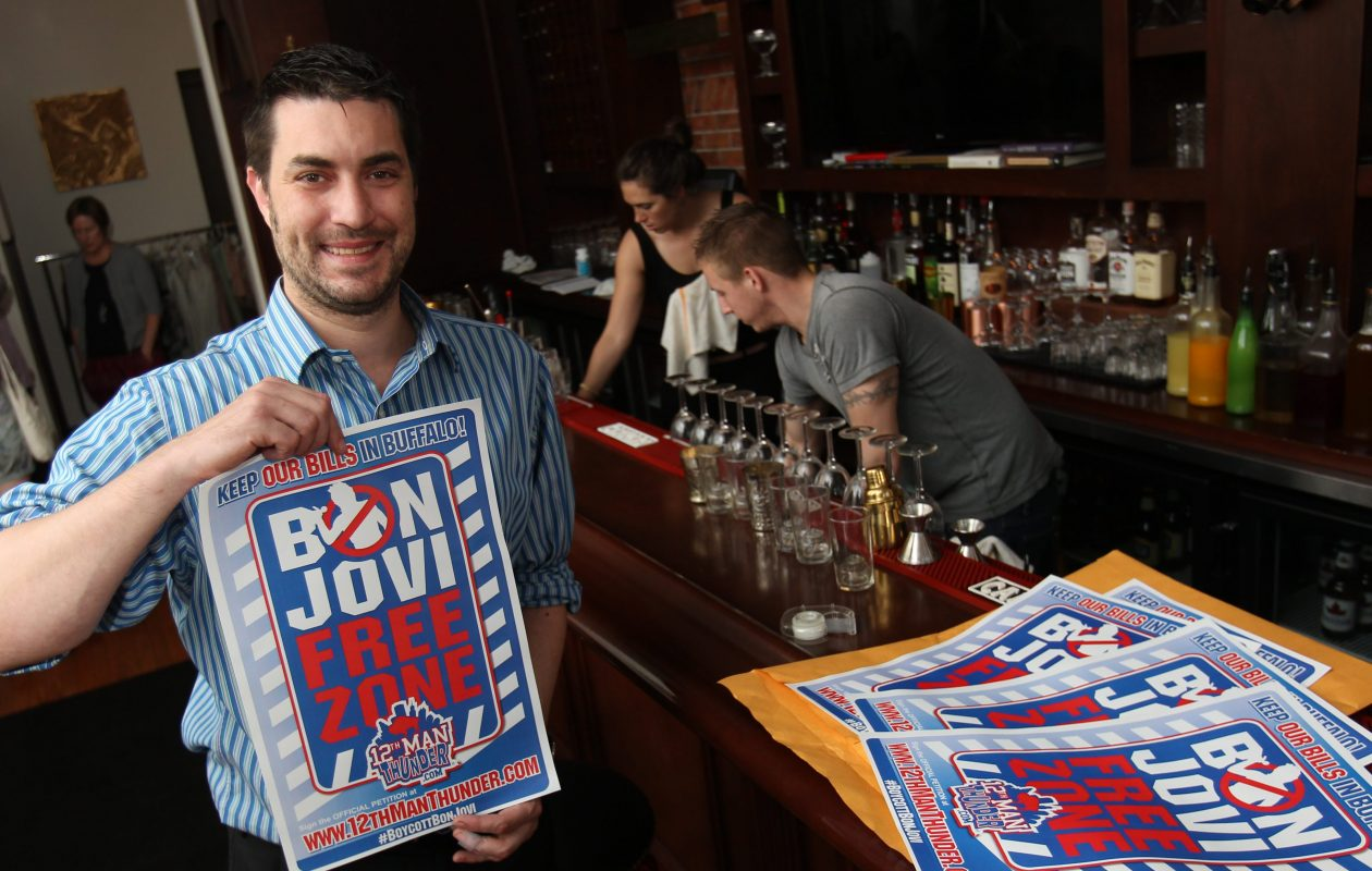 Anthony Lynch hangs a 'Bon Jovi Free Zone' poster at Savoy on Elmwood Avenue in Buffalo on May 21, 2014. (Sharon Cantillon/News file photo)