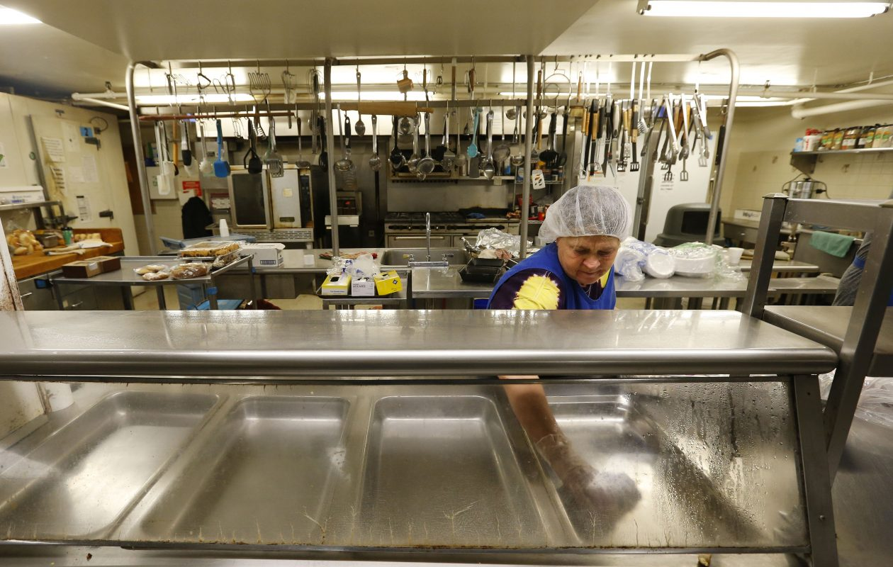 Norma Bigelow cleans up after serving lunch at the Community Missions of Niagara Frontier in Niagara Falls on Jan. 12, 2017.  (Mark Mulville/The Buffalo News)