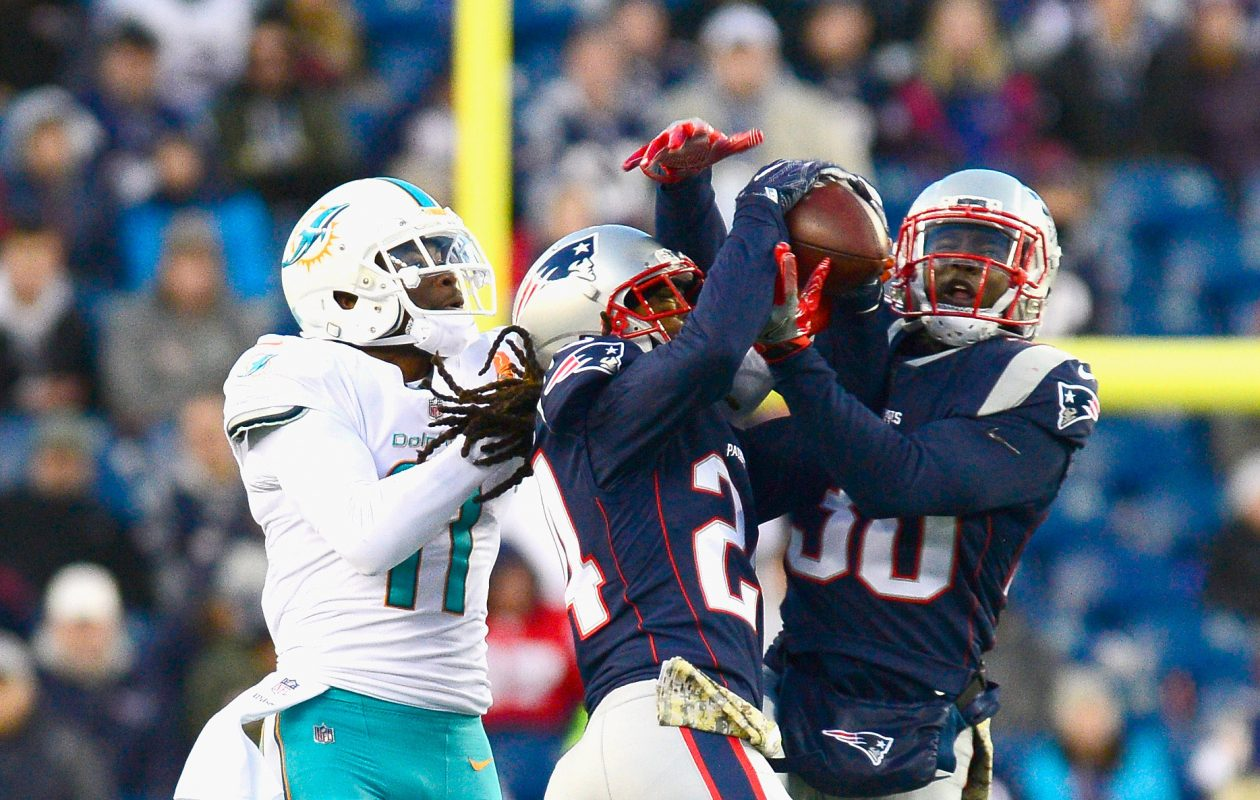 Stephon Gilmore #24 and Duron Harmon #30 of the New England Patriots intercept a pass intended for DeVante Parker #11 of the Miami Dolphins during the fourth quarter of a game at Gillette Stadium on November 26, 2017 in Foxboro, Massachusetts.  (Photo by Adam Glanzman/Getty Images)
