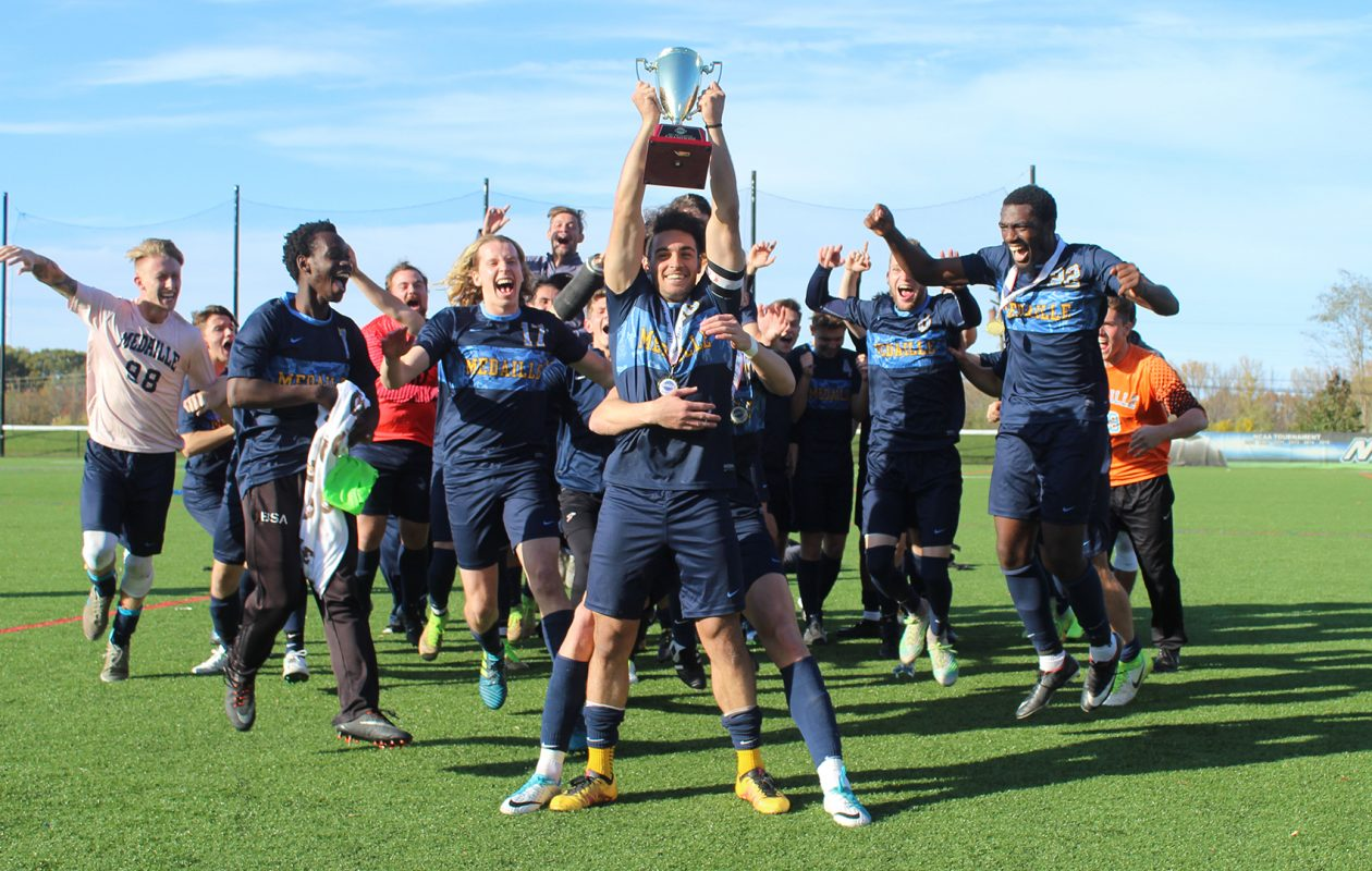 Medaille mens soccer celebrates with the AMCC trophy after winning the programs first conference title since 2012. (Photo courtesy of Medaille athletics)