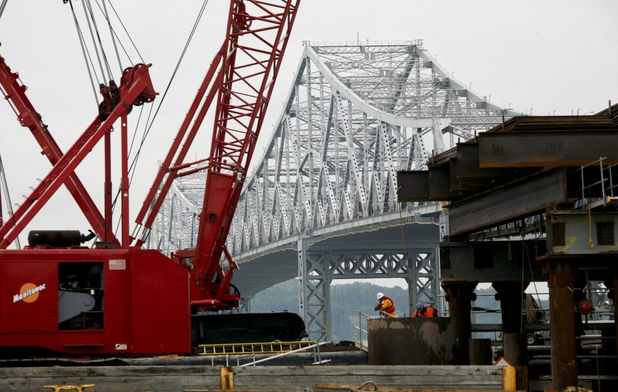 """Workers near the Tappan Zee Bridge in Tarrytown, N.Y., on May 30, 2012.   Legislation that was passed by the New York State Legislature earlier this year and which Gov. Andrew Cuomo is expected to sign into law would require all state bridge and road projects with procurement over $1 million must include iron and steel """"produced or made in whole or substantial part in the United States, its territories or possessions."""" (Librado Romero/The New York Times)"""