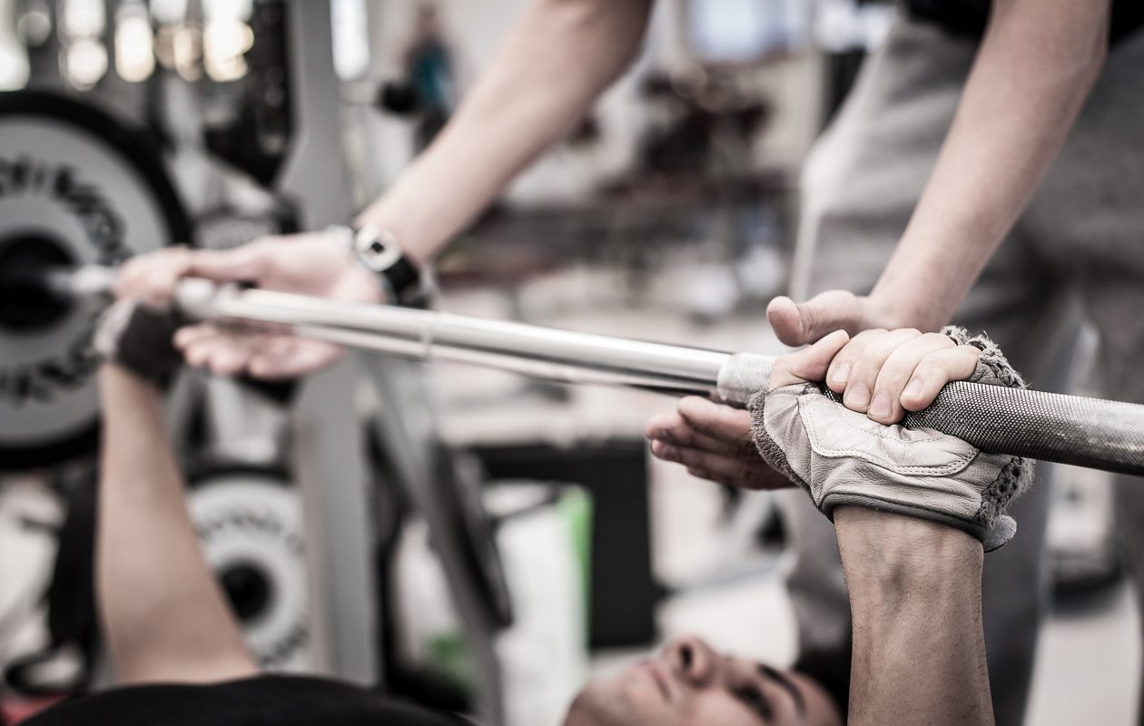 Young man lifts a barbell in the gym with instructor.