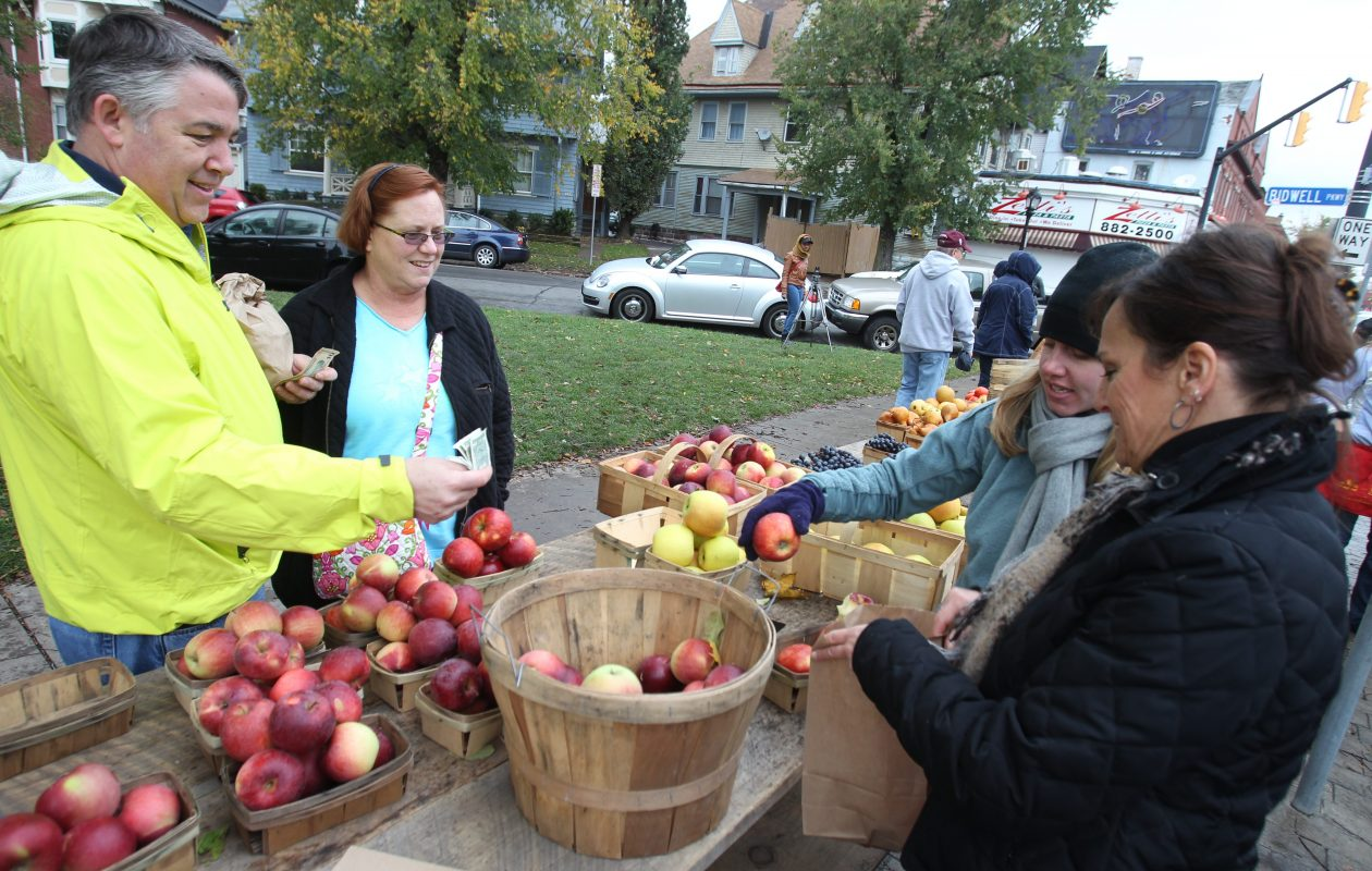 Doug and Laurie Brown buy apples from Caitlin Tyo and Cindy Nostro who work for Tom Towers Farm at the Elmwood Village Farmers Market. An eight-week indoor holiday market will start Nov. 25 inside St. John's Grace Episcopal Church, 51 Colonial Circle.  (John Hickey/News file photo)