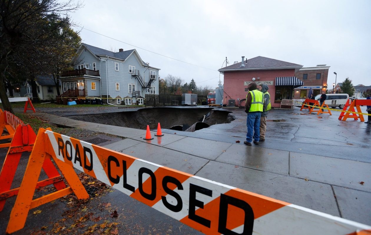 Workers close off a parking lot Nov. 6 where a sink hole opened up the night before next to Mikey Dee's Cafe and Catering on Main and S. Willow streets in the Village of East Aurora. (Mark Mulville/Buffalo News)