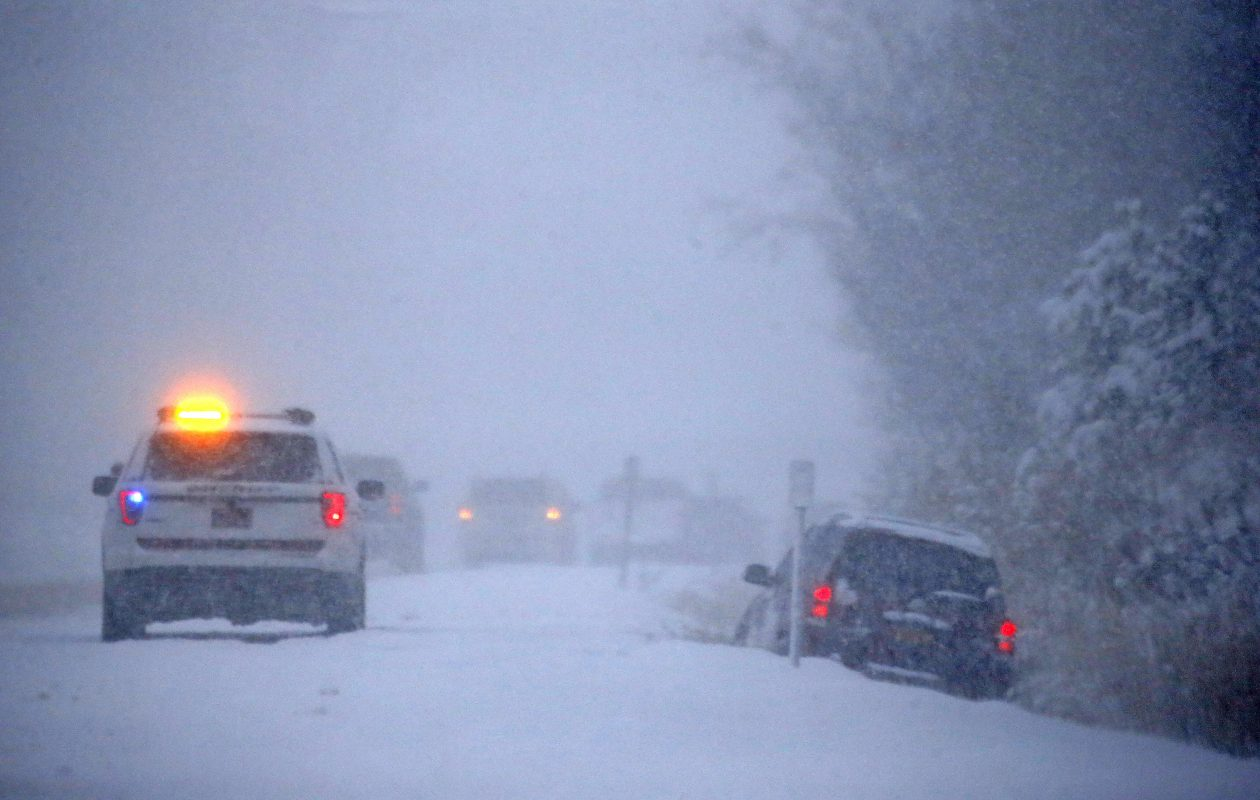 A motorist stays warm in a car after sliding off the highway in the northbound lane of Route 400 in Elma Thursday.  A persistent lake-effect snow band stalled over Elma and East Aurora, quickly dumping snow.  (Robert Kirkham/Buffalo News)