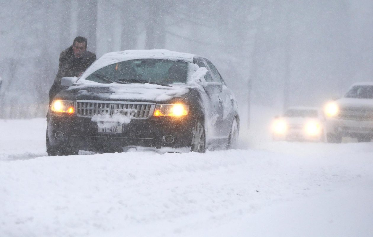 A person tries to push a car out of a snowbank on Union Road in West Seneca on Dec. 10. (Mark Mulville/Buffalo News)