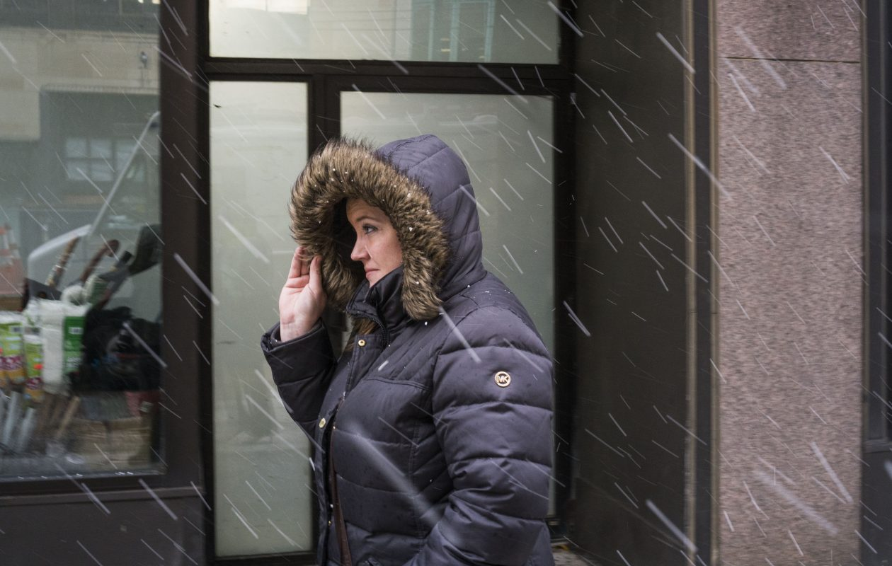 Courtney Ennis braces herself from the wind and snow as she walks down Main Street during her lunch break on Wednesday, Dec. 6, 2017.  (Derek Gee/Buffalo News)