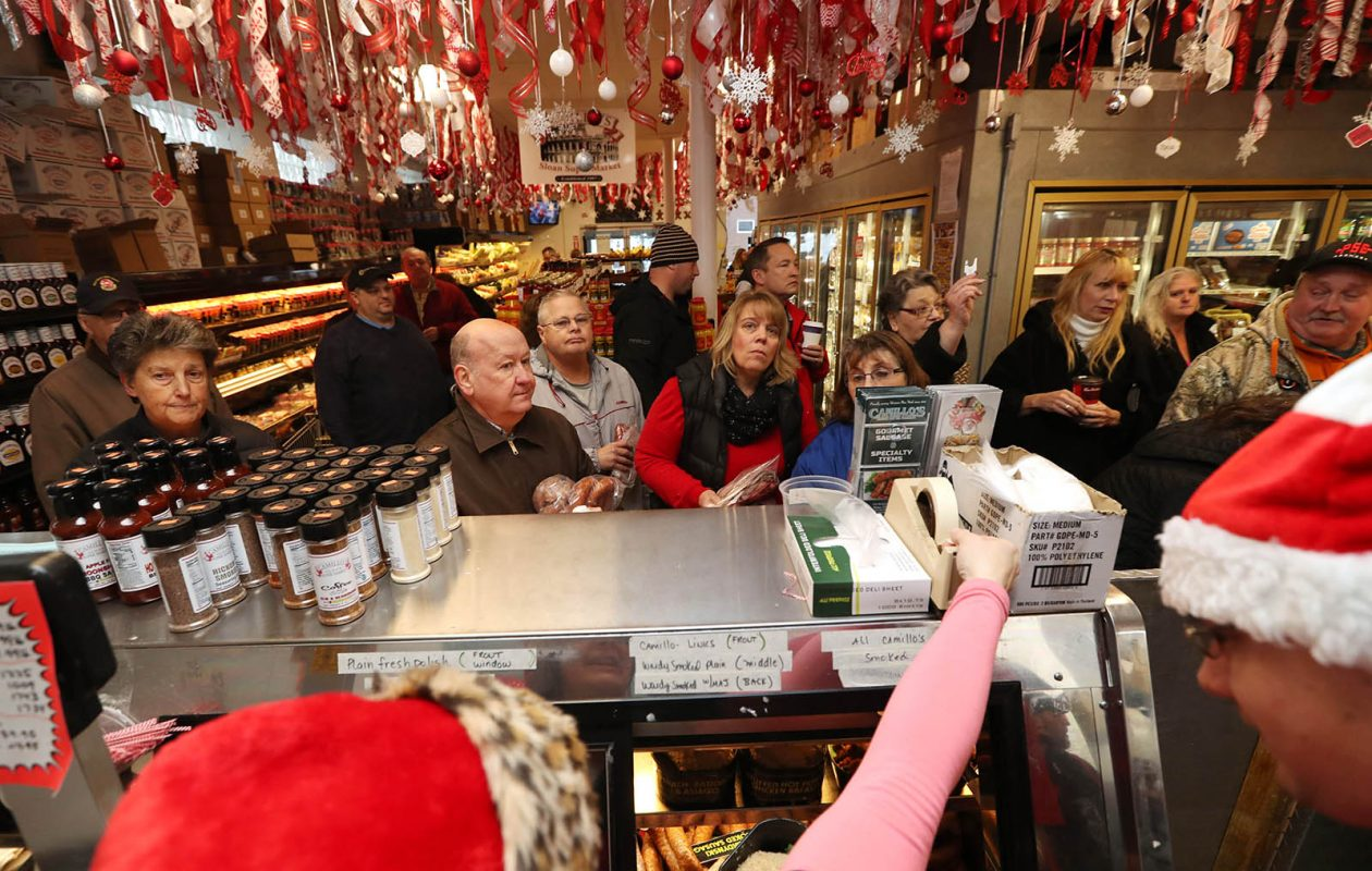 Customers arrive at Camillo's Sloan Super Market on Dec. 22 to pick up their holiday meat orders.  Customers go straight to the meat counter and wait for their number to be called.  (Sharon Cantillon/Buffalo News)