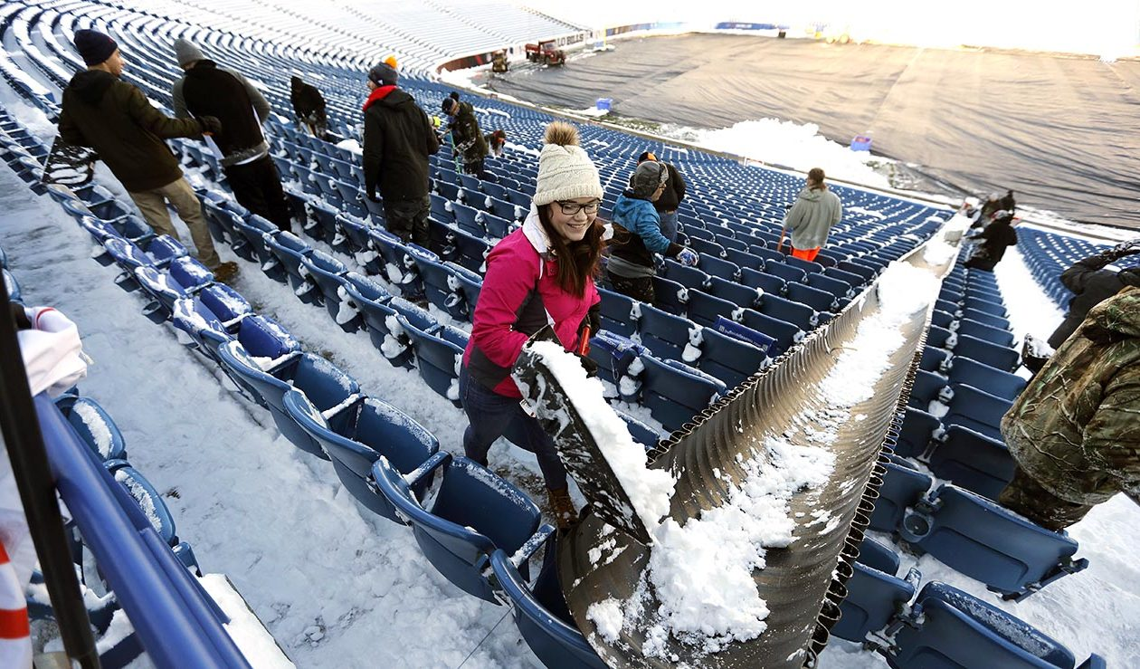 Shovelers clear seats of snow using a chute in the lower bowl of New Era Field in Orchard Park on Dec. 8. Crews were getting ready for this Sunday's game with the Colts.    (Mark Mulville/News file photo)
