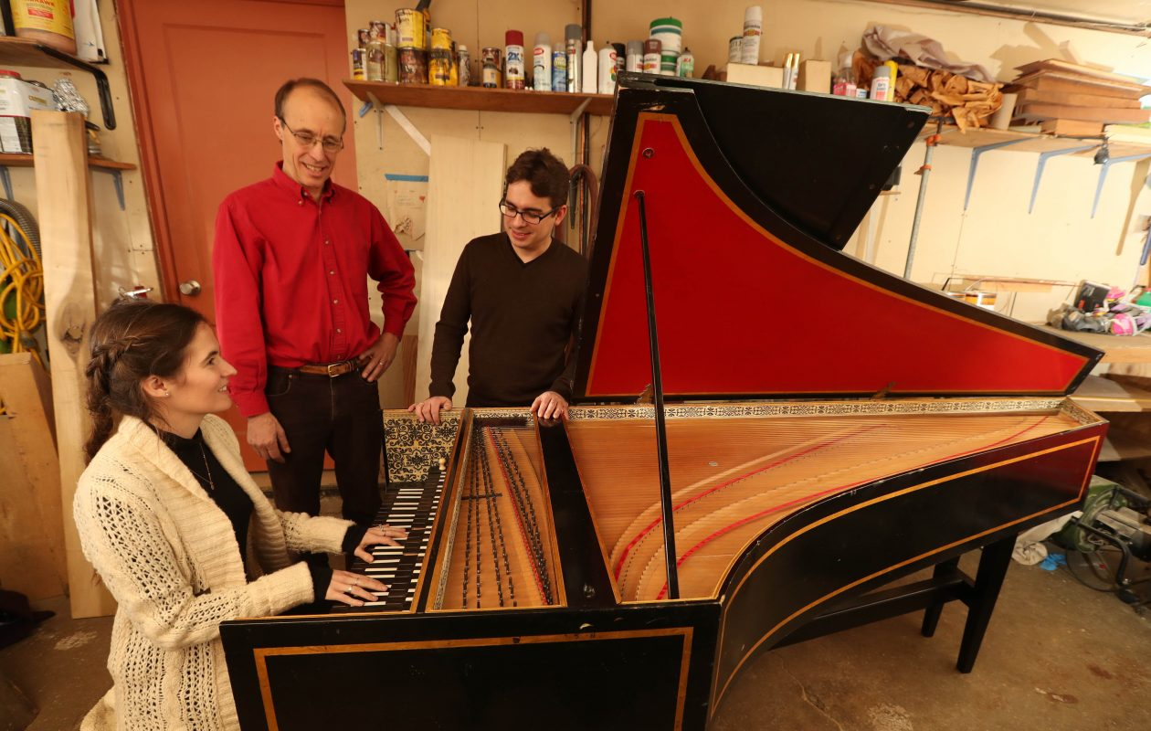 The Buffalo Chamber Players are raising money  to complete the renovation of a harpsichord that was discovered in the catacombs of Kleinhans Music Hall.  Abigail Rockwood Puehn, harpsichord player for the Buffalo Chamber Players, tries out the instrument.  Looking on is Bob Sowyrda, center, and Janz Castelo, artistic director for the Buffalo Chamber Players. (Sharon Cantillon/Buffalo News)