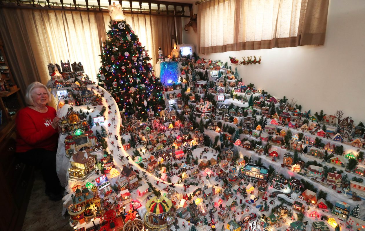 Carol Heusinger shows off Carol's Village, her little Christmas world that has taken over a room in her house in December for the last 53 years.  The tradition began with her father, and she took over where her father left off.  She has taken it to the next level with hundreds of pieces, lights and many moving parts. (Sharon Cantillon/Buffalo News)