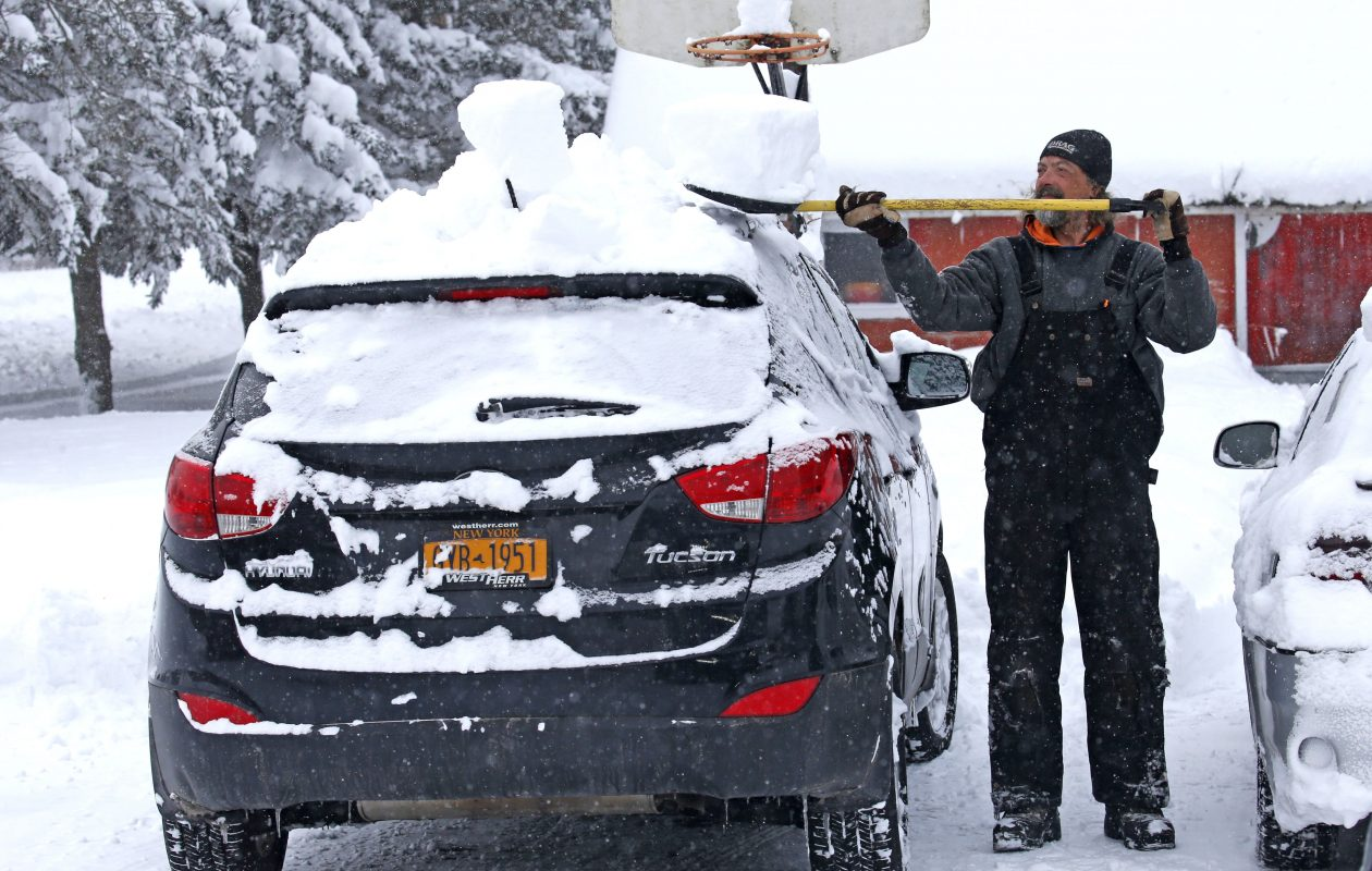 James Bushey of Lancaster cleans snow off the roof of his girlfriend's car in the Village of Arcade on Tuesday, Dec. 26, 2017.  (Robert Kirkham/Buffalo News)
