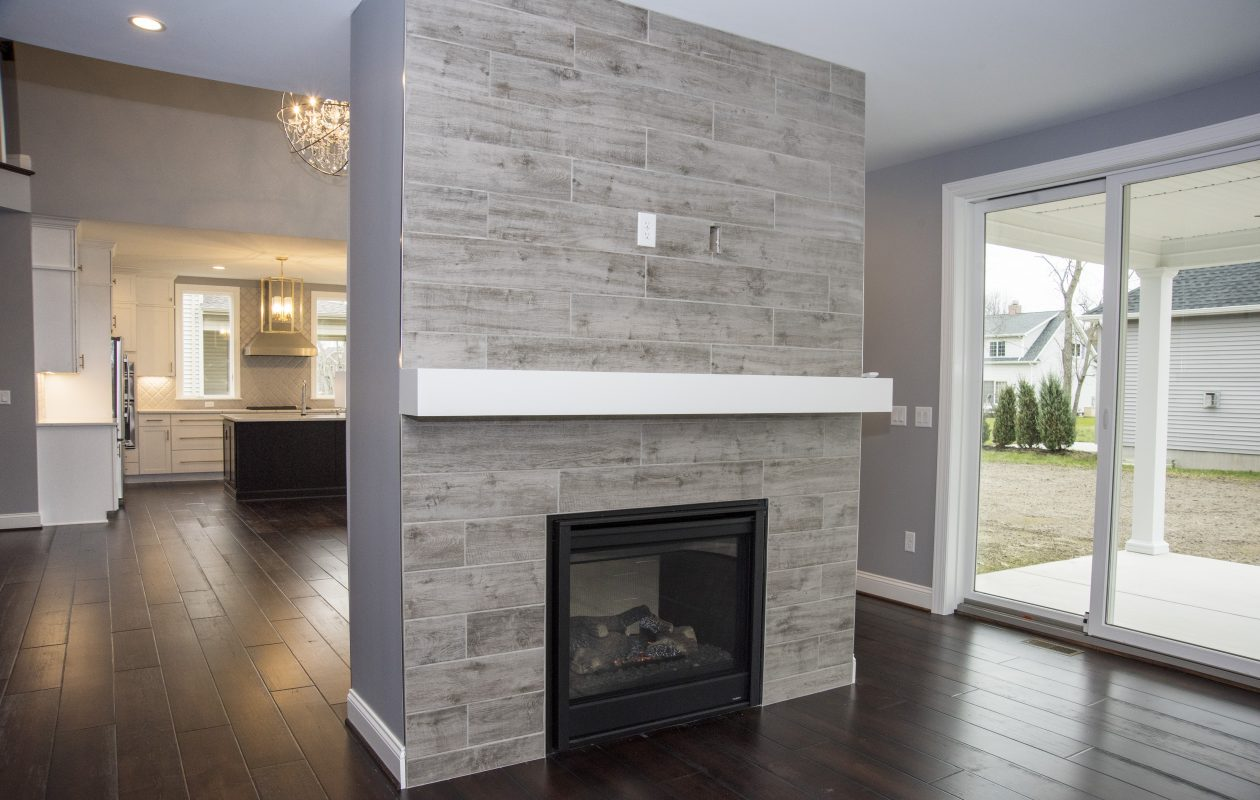 A double sided fireplace sets off the sunroom from the main open floorplan.